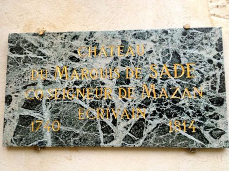 The plaque on the chateau wall, indicating de Sade's ownership.