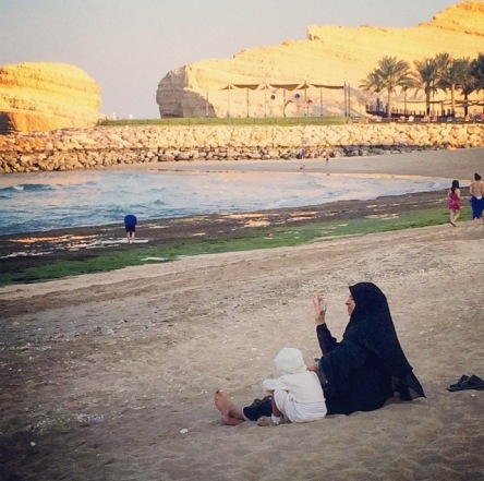 A curious blend of the modern and the traditional. Clad in her a abaya, a resort guest checks messages on her smartphone.